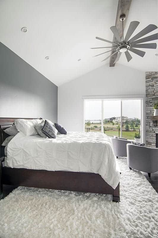 This is a simple bedroom with a tall cathedral ceiling, a gray wall behind the brown headboard of the bed and a stone fireplace on the other side by the window.