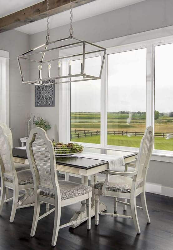 This is a bright dining area with a sleek stainless steel lighting over the rectangular dining table contrasted by the white chairs and brightened by the large windows.