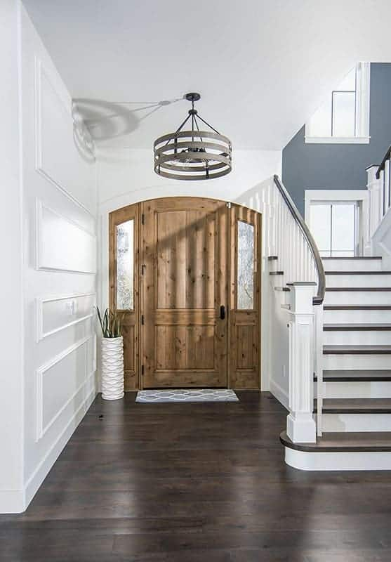 This is a simple foyer with a dark hardwood flooring contrasted by the white walls and tall ceiling that hangs a round lighting over the wooden main door.