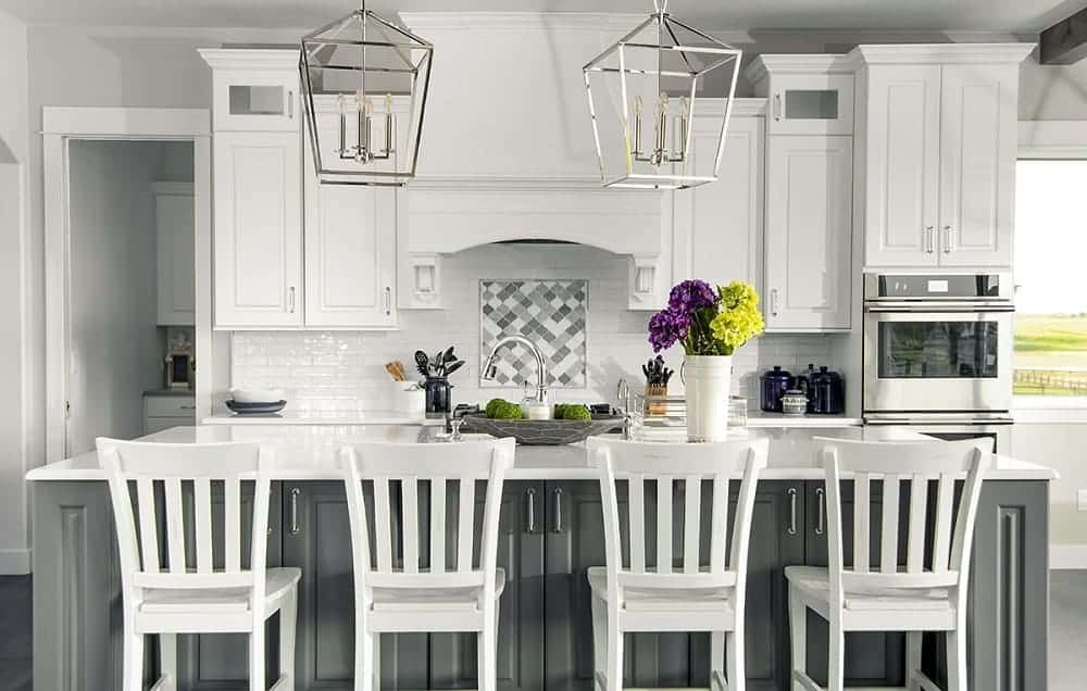 This is a bright kitchen with white shaker cabinets on the walls and gray kitchen island topped with a white counter and paired with white stools.