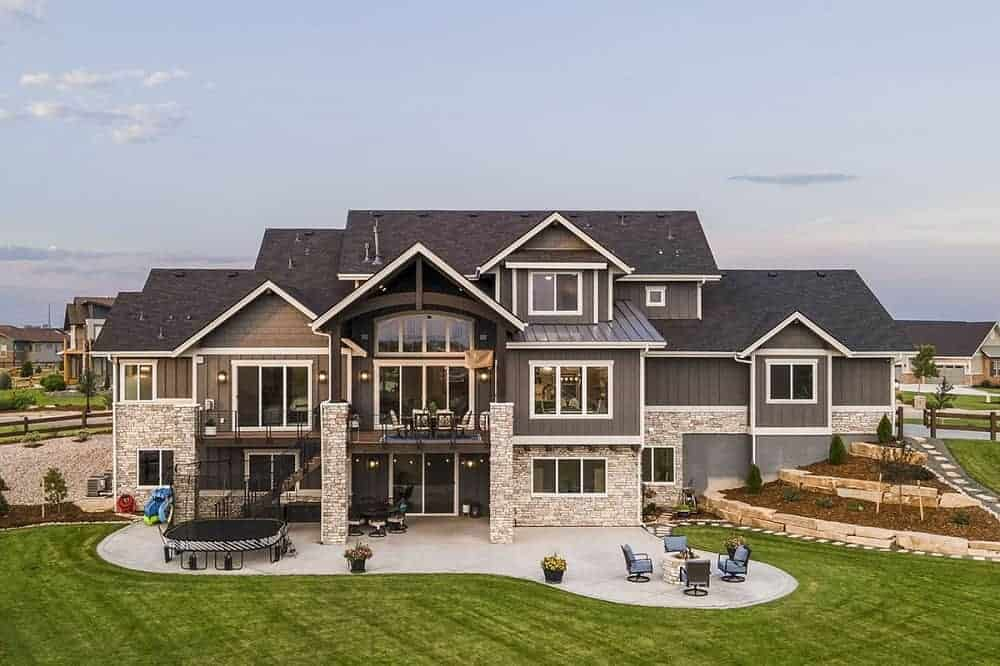 This is an aerial view of the back of the house that has a fire pit area and a trampoline area by the grass lawn and a large planter on the side of the house with terraces.
