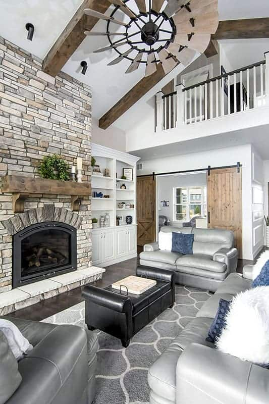 The living room has a tall ceiling with an indoor balcony looking over the gray sofa set and dark cushioned coffee table across from the mosaic stone fireplace.