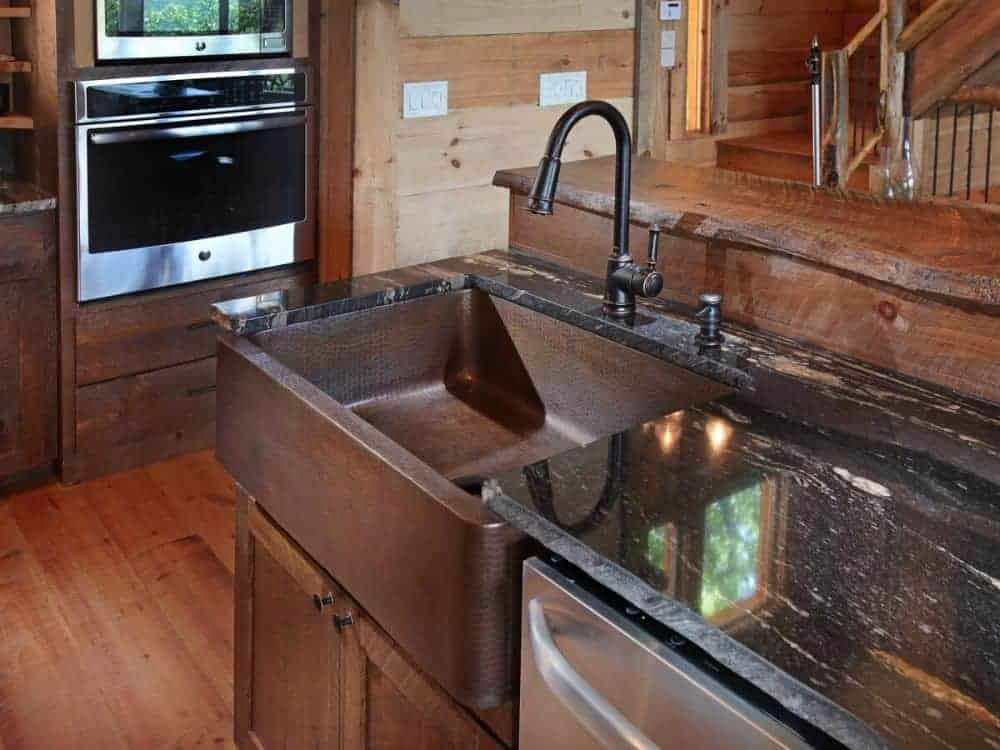 The kitchen island is fitted with a dishwasher, a farmhouse sink, and a gooseneck faucet in a wrought iron finish.