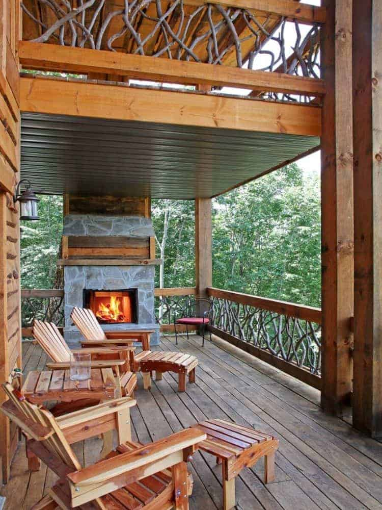 Covered deck with wooden seats and an outdoor fireplace accentuated with stones.