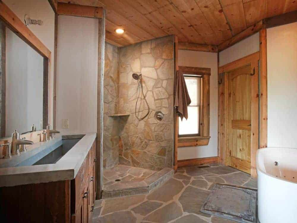 The primary bathroom is equipped with a trough sink vanity, a bathtub, and a walk-in shower with stone walls that extend into the flooring.