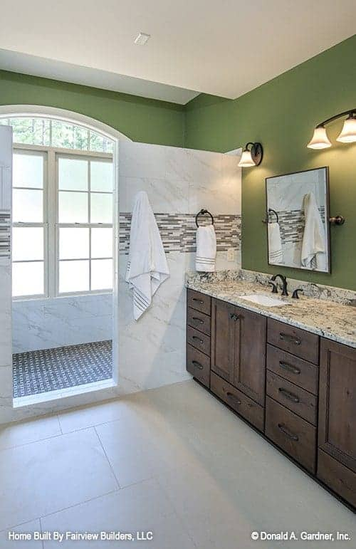 This is the bathroom with avocado green walls to pair with the dark wooden two-sink vanity on the side of the marble wall of the shower area on the far side by the window.