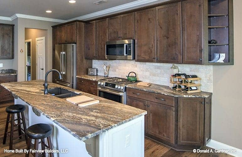 This is a close look at the kitchen dominated by the dark wooden cabinetry lining the walls contrasted by the white backsplash that matches the kitchen island topped with a gray marble countertop.