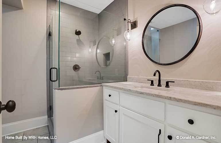 This is a simple bathroom that has beige walls complemented by the white cabinets of the vanity, glass walls of the shower area and the round mirror that matches the black fixtures.