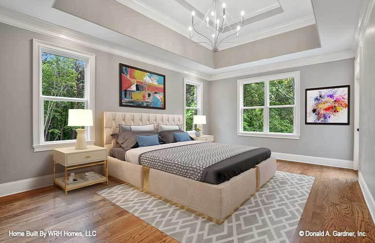 The primary bedroom has a beige tufted and cushioned bed that matches the beige bedside drawers. These are then complemented by the patterned area rug, decorative chandelier and the colorful wall-mounted artwork above the headboard.