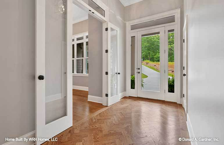 This is a simple foyer with a glass main door that brings in natural lighting for the herringbone hardwood flooring that complements the light gray walls with white accents.