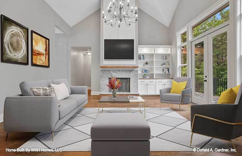 This is a look at the living room that has a tall cathedral ceiling and a fireplace at the far wall across from the gray sofa set that pairs well with the decorative chndelier and the patterned area rug.
