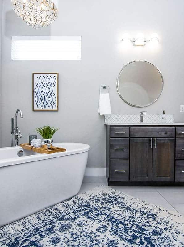 This is a close look at the bathroom showcasing the white porcelain freestanding bathtub beside the dark wooden vanity topped with a round mirror and wall sconces. These are then complemented by the decors and windows.