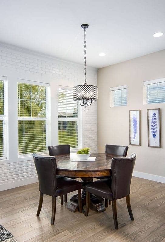 This is a close look at the simple dining area with a dark wooden round table surrounded by dark brown upholstered chairs and topped with a simple drum pendant light hanging from a white ceiling that matches the white brick wall.
