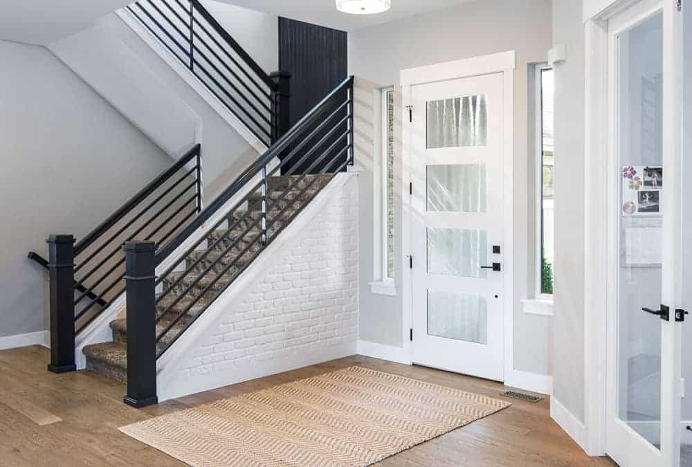 This is a close look at this foyer with bright white walls to match the white main door that has glass panels. These are contrasted by the dark gray railings of the staircase on the side.