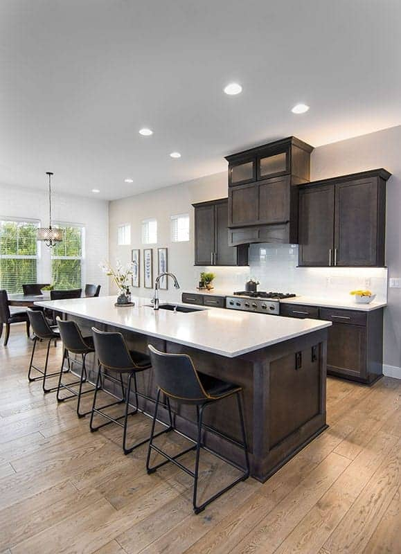 This is a close look at an eat-in kitchen with dark wooden tones on its cabinetry and kitchen island contrasted by the white counter and backsplash of the cooking area.