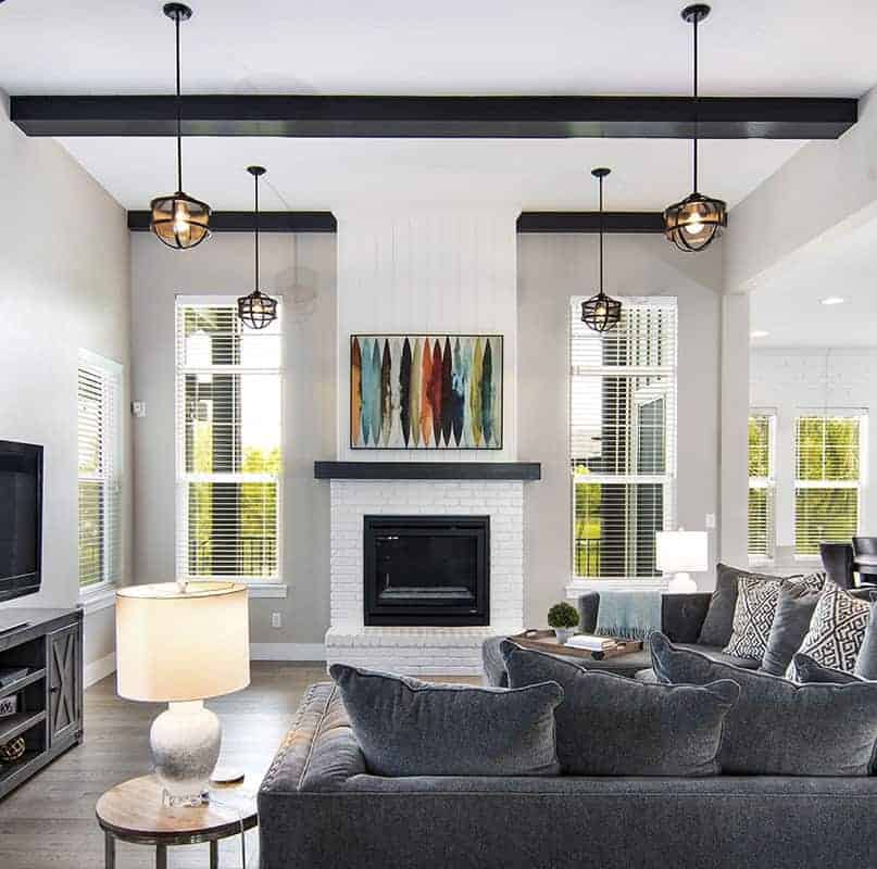 This is a close look at the living room that is dominated by the large dark gray sectional sofa with end tables paired with a white fireplace and topped with multiple pendant lights.