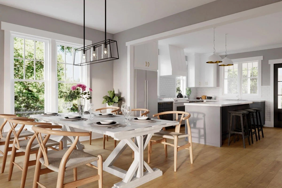 Dining area with wooden round back chairs and a white rectangular dining table illuminated by a wrought iron chandelier.