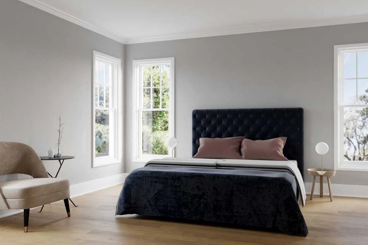 The primary bedroom features lots of windows, a beige contemporary chair, and a tufted bed over the hardwood flooring.
