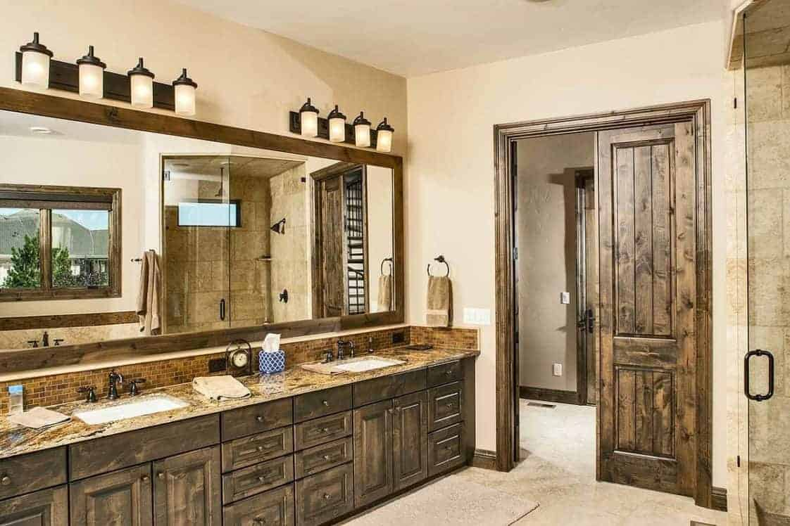 The primary bathroom has a large two-sink wooden vanity that matches well with the doors and the frame of the mirror topped with sconces across from the glass-enclosed shower area.