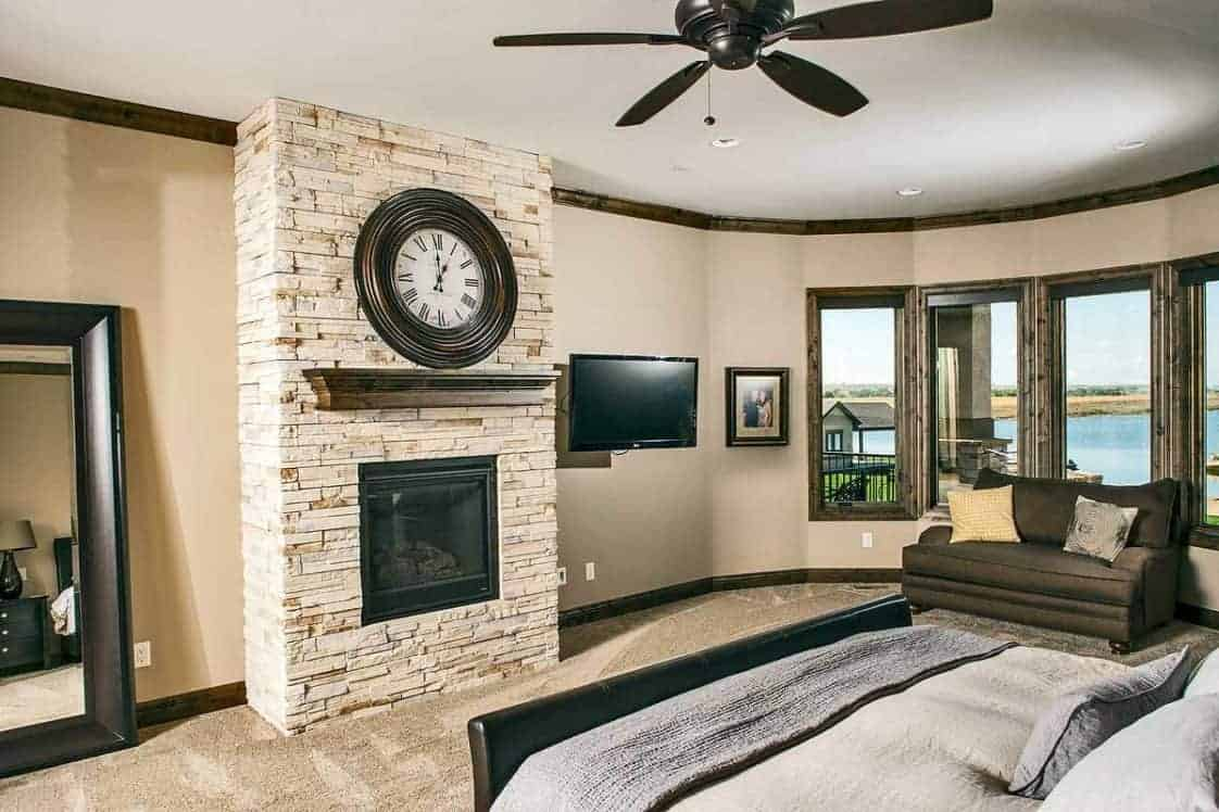 This is the primary bedroom with a black wooden sleigh bed across from the stone mosaic fireplace topped with a large round clock. On the side is a reading nook by the windows.