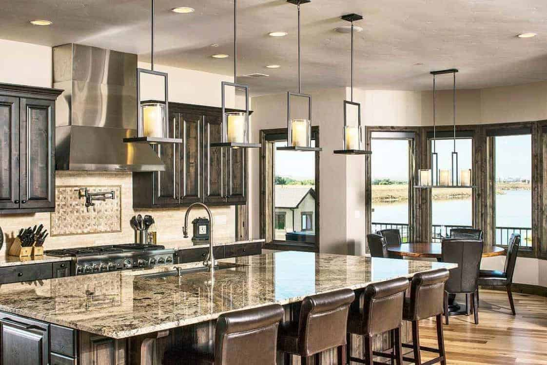 This is the spacious eat-in kitchen with dark brown wooden cabinetry, a large kitchen island topped iwth pendant lights and a breakfast nook on the far side with a round wooden dining table by the windows.