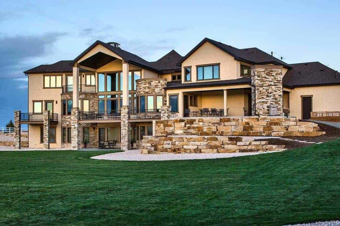 This is a look at the back of the house that has multiple stone mosaic structures and wall panels to match the landscaping of mosaic stone terraces and graveled soil contrasted by the large grass lawn.