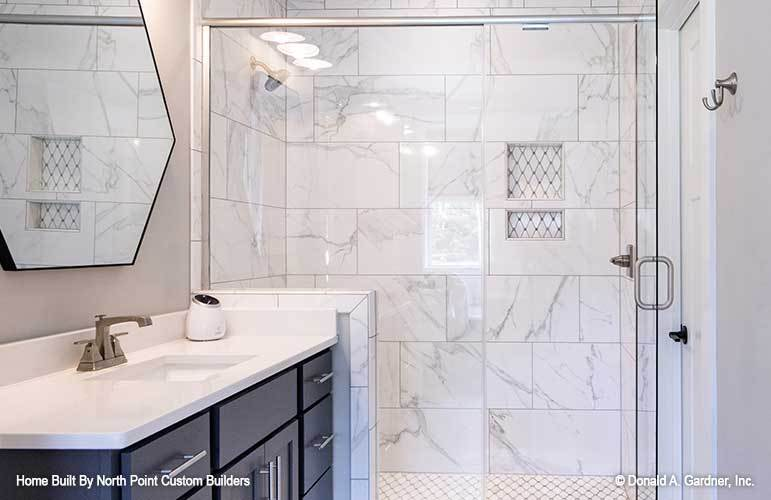 This is a close look at the bathroom that has a glass-enclosed shower area with white marble tiles on its walls and floor. This is contrasted by the dark modern drawers and cabinets of the vanity beside it.