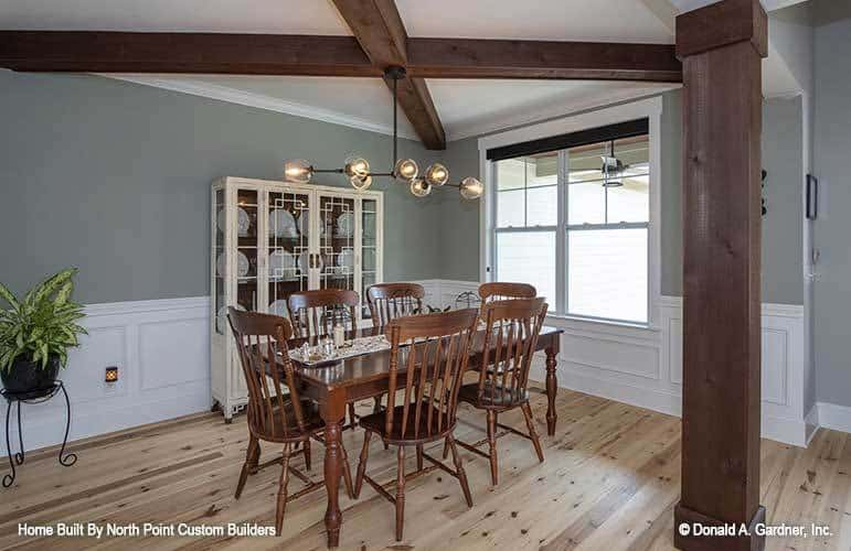 This simple dining room is dominated by the dark wooden cross beams exposed at the ceiling that matches with the wooden pillar on the side and the wooden dining set on the hardwood flooring.