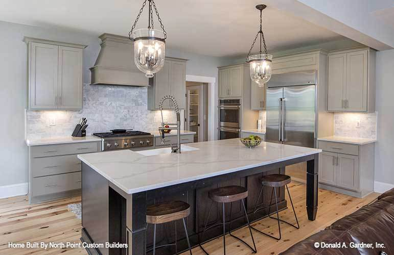 The kitchen is dominated by a large dark wooden kitchen island in the middle that has a white marble counter topped with a couple of glass pendant lights hanging from the white ceiling.