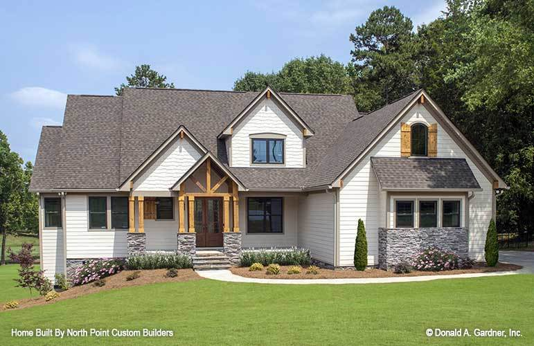 This is a view of the front exterior of the house that has a concrete walkway in the middle of a grass lawn and the soil on the side of the house planted with various shrubs to complement the white shiplap walls.