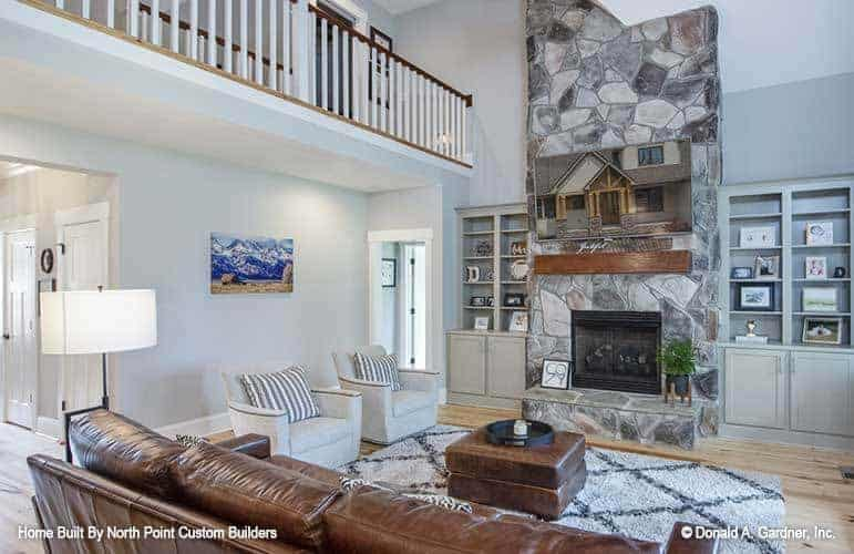 The living room has a tall ceiling with an indoor balcony looking over the brown leather sofa and ottoman across from the stone mosaic fireplace.