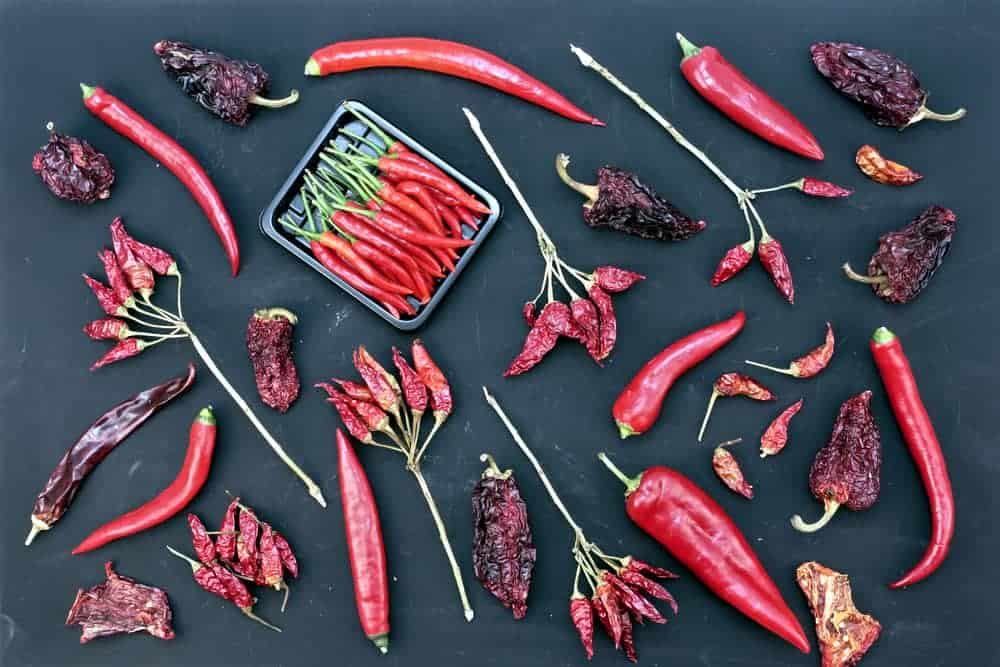 This is a close look at various different types of chili on a dark surface.
