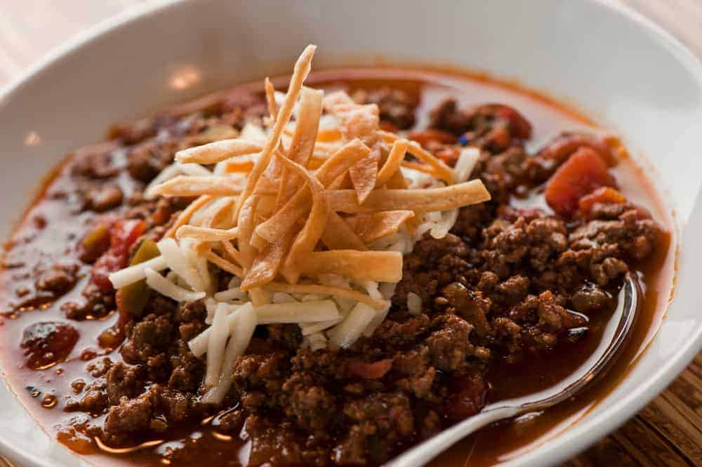 This is a close look at a bowl of Texas five alarm chili with toppings.