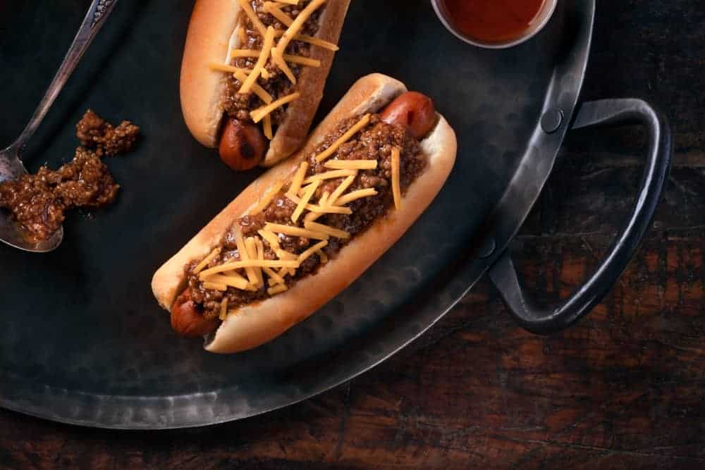 A close look at a couple of chili dogs on a hot plate.