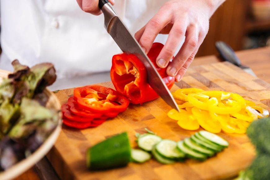 A close look at a chef cutting up colorful vegetables.