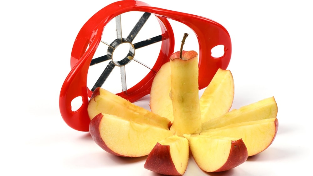 A close look at an apple slicer with a sliced apple.