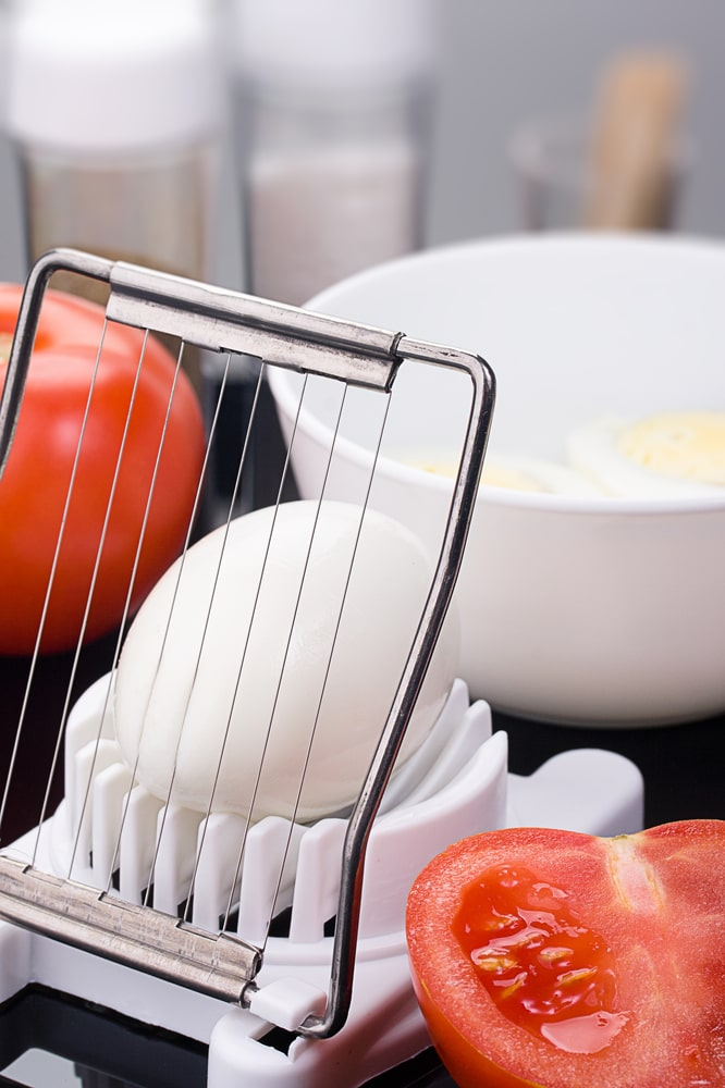 A close look at an egg slicer in action.