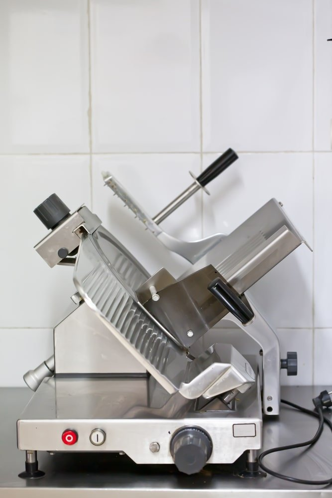 A close look at an electric meat slicer.