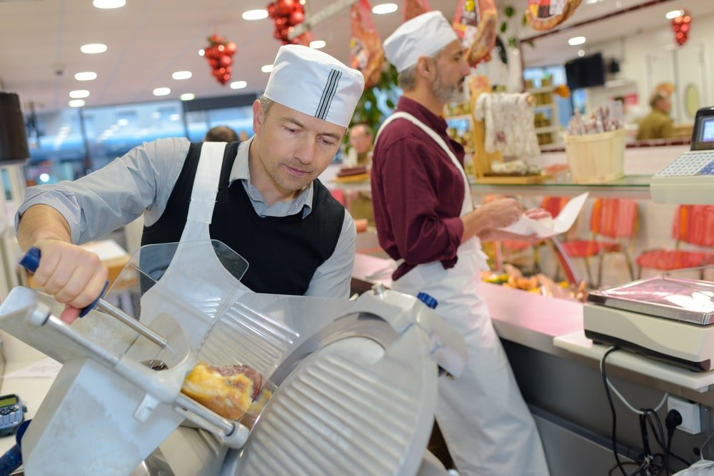 A man using a commercial meat slicer at a meat market.