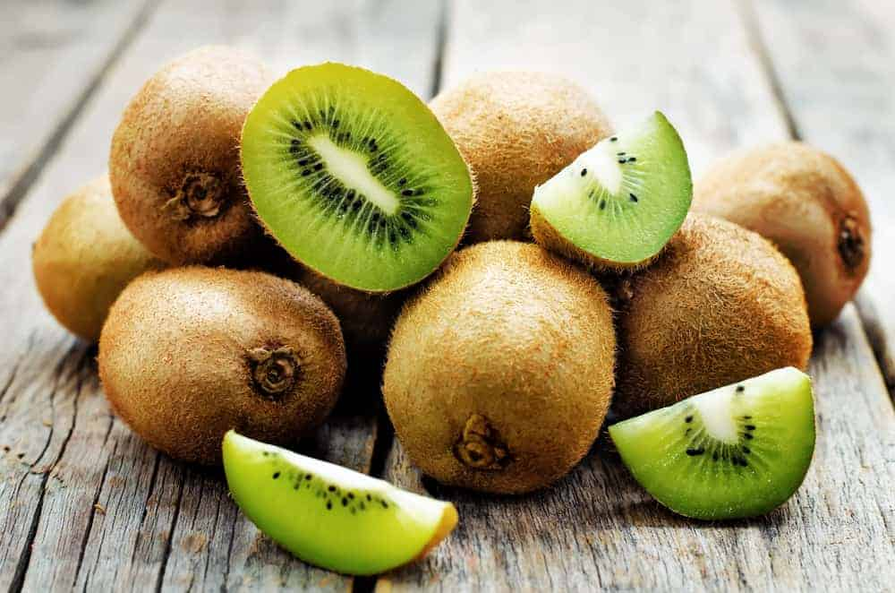 This is a close look at a bunch of kiwi fruits on a wooden table.