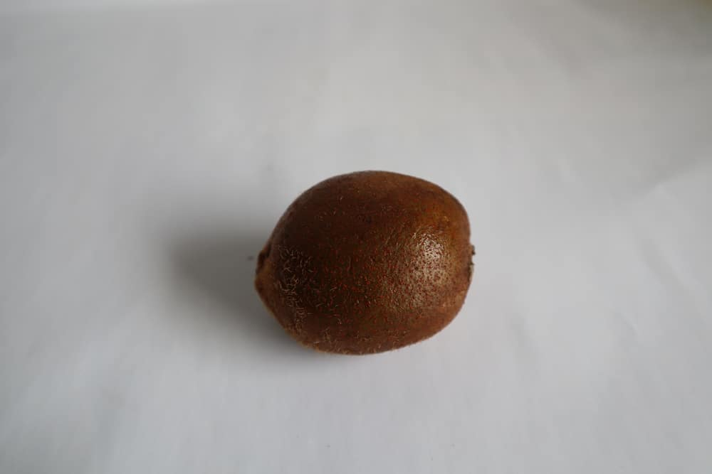 A single piece of Chinese Egg Gooseberry on a white surface.