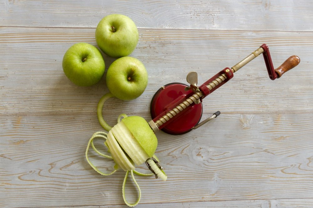 A mechanical peeler with apples.