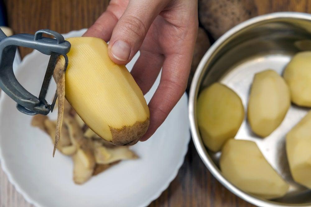 A potato being peeled with a potato peeler.