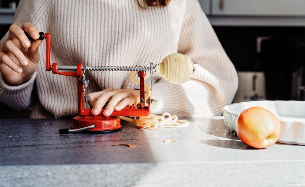 A woman peeling apples with an apple peeler.