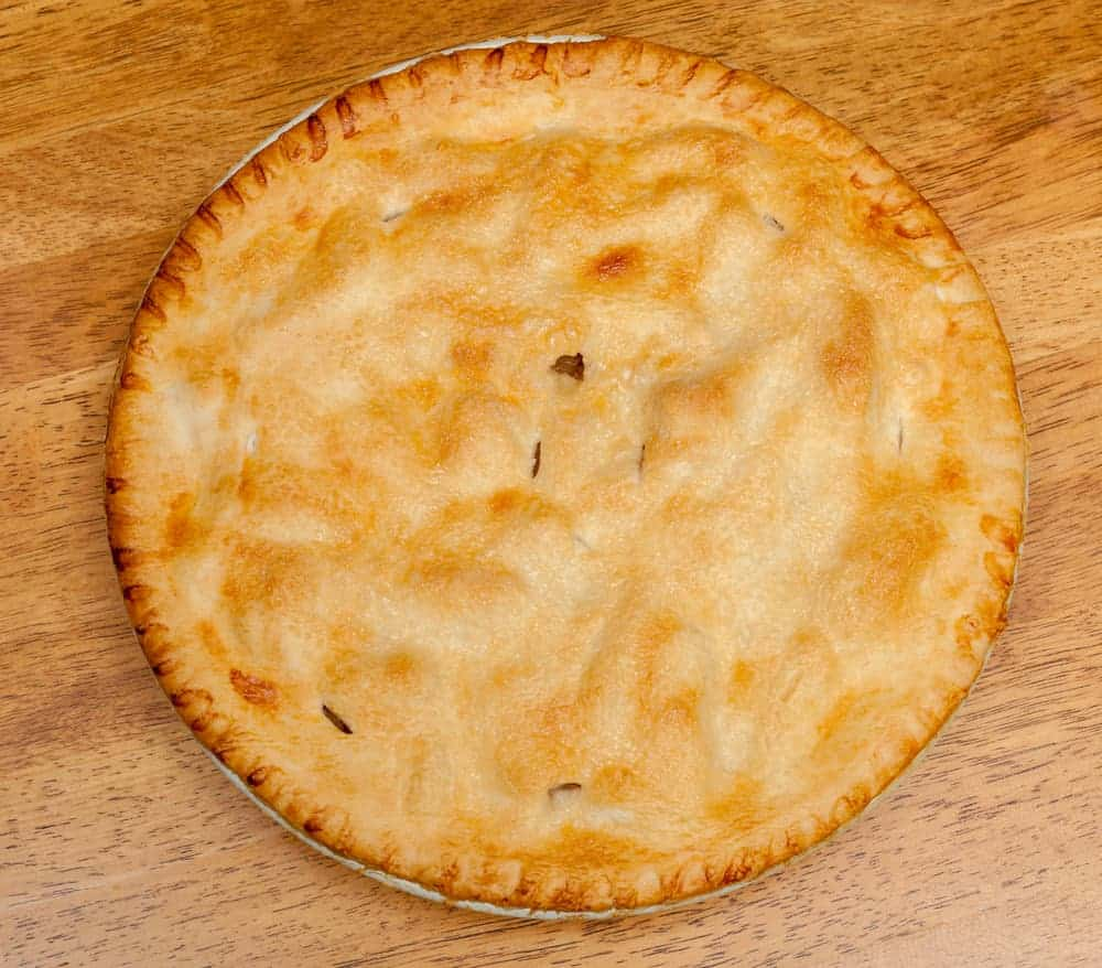 This is a freshly-baked apple pie in a round pie pan.