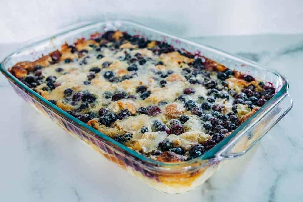 A rectangular blueberry cobbler pie baked in a rectangular glass dish.