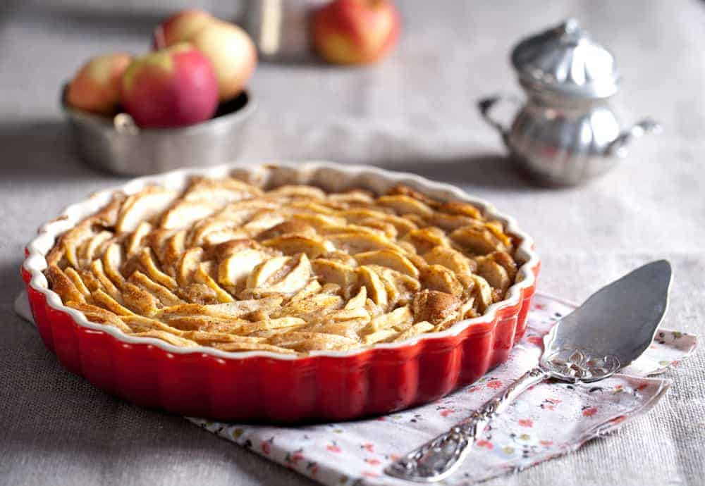 This is a close look at an apple pie in a ceramic dish.