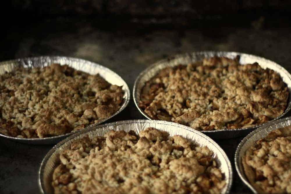 A close look at a few crumble pies inside aluminum pans.