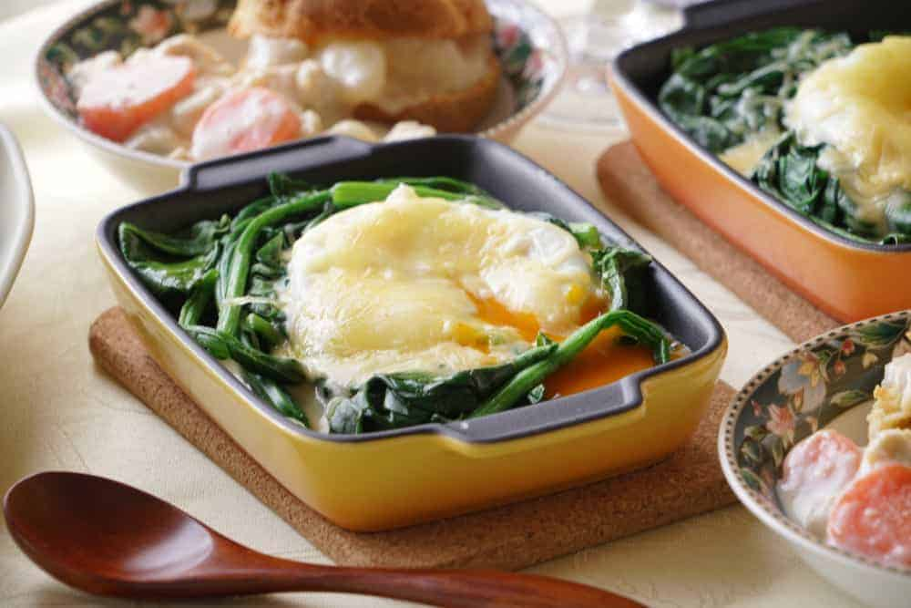 A close look at spinach and egg served in pyrex pie pans.