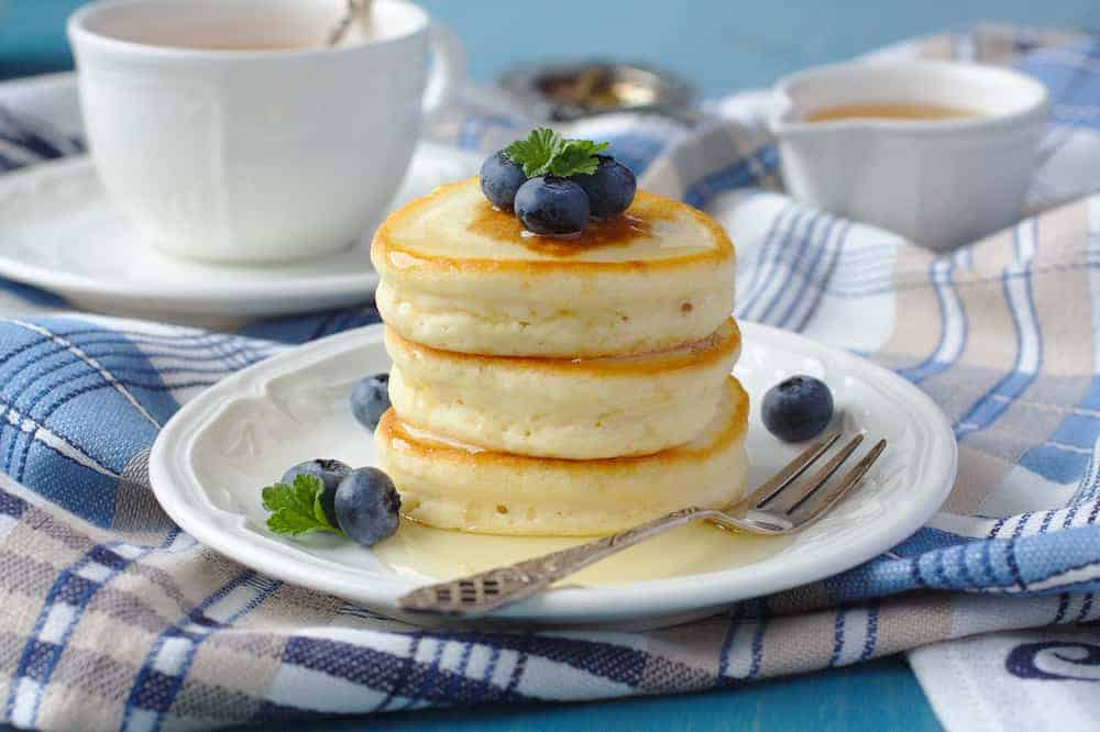 A stack of drop scones on a plate with blueberries.